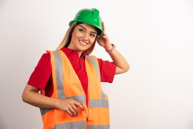 保護制服と白い背景の上のヘルメットのポーズで笑顔の女性。