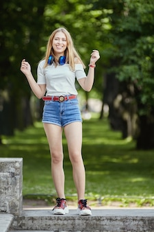 공공 공원에서 웃는 여자. 반바지와 플랫폼 신발에 약 20 세 쾌활한 아름다운 백인 소녀가 정원 파빌리온에 서 있습니다.