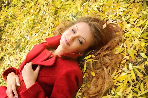 Улыбающаяся женщина в красном пальто, лежа в осенних листьях в парке.