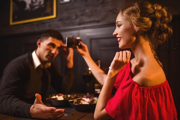 빨간 드레스에 웃는 여자는 전화 카메라에 그녀의 남자의 이미지를 만든다. 레스토랑에서 아름다운 사랑의 커플, 낭만적 인 저녁, 기념일 축하