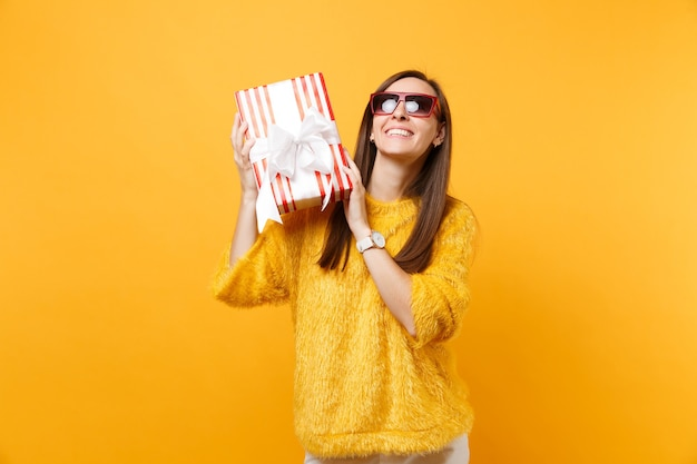 贈り物と赤い箱を持って見上げる赤い眼鏡の笑顔の女性、祝って、明るい黄色の背景で隔離の休日を楽しんでいます。人々は誠実な感情、ライフスタイル。広告エリア。