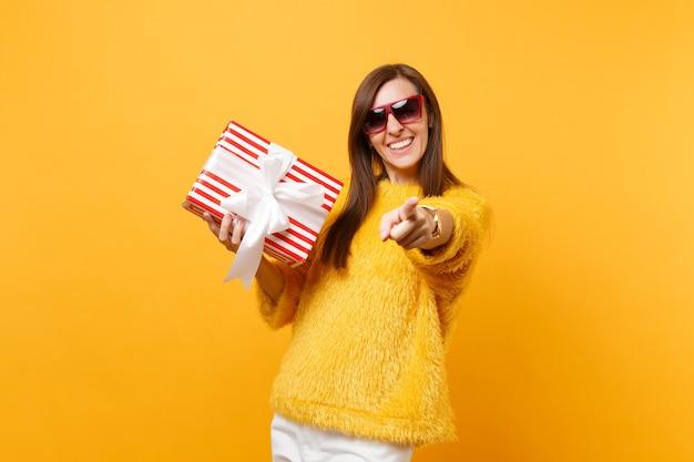 カメラに人差し指を指し、ギフトと赤い箱を保持し、明るい黄色の背景で隔離の存在の赤い眼鏡で笑顔の女性。人々の誠実な感情、ライフスタイルのコンセプト。広告エリア。