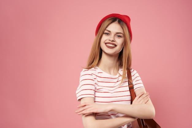 赤い帽子のファッショナブルな服の感情ピンクの背景で笑顔の女性。高品質の写真
