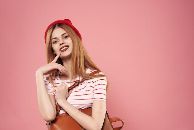 赤い帽子のファッショナブルな服の感情ピンクの背景で笑顔の女性