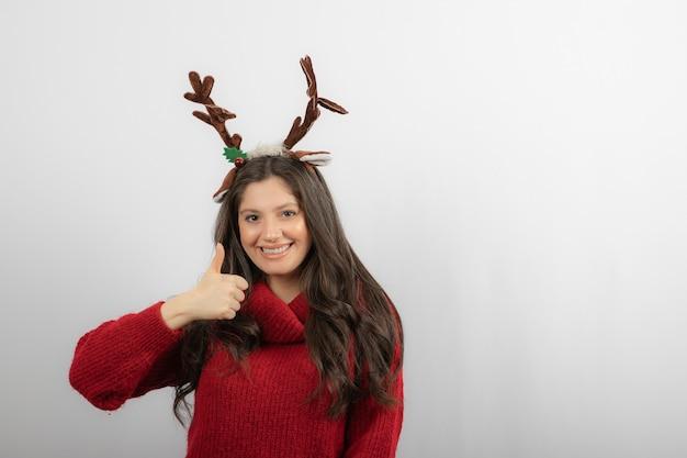 親指を上に表示している赤い暖かいセーターと鹿のヘッドバンドで笑顔の女性。