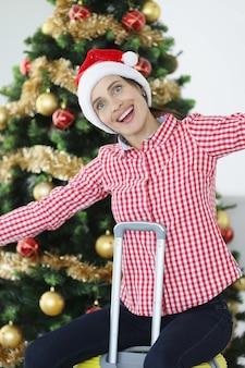 クリスマスツリーの旅を背景に、サンタクロースの帽子をかぶった笑顔の女性がスーツケースに座っています。