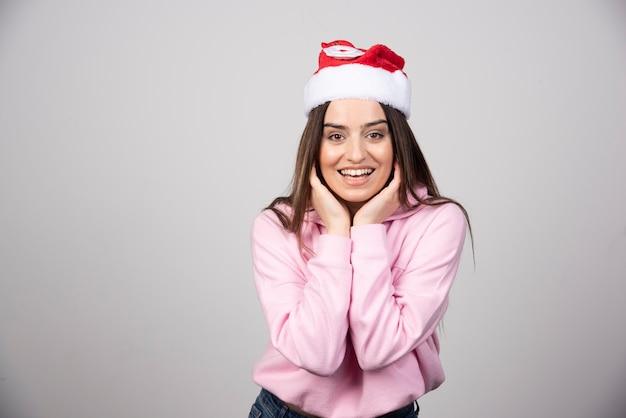 髪を修正するサンタクロースの赤い帽子の笑顔の女性。