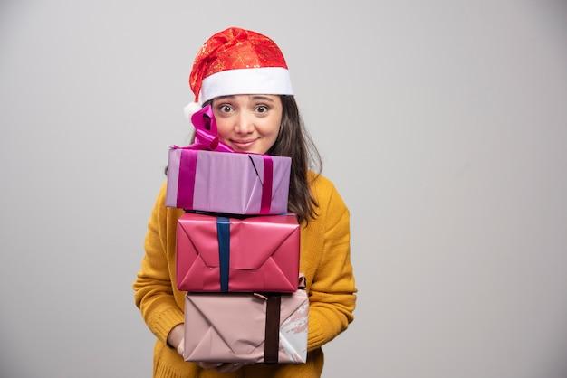 산타 모자 선물 상자를 들고 웃는 여자.