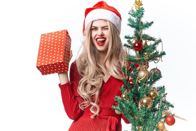 サンタ帽子の休日の感情ギフトクリスマスの笑顔の女性