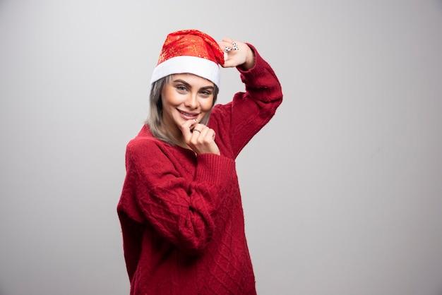 회색 배경에 포즈를 취하는 산타 모자에 웃는 여자.