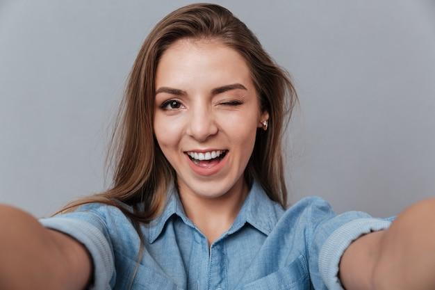 スタジオとウィンクでselfieを作るシャツで笑顔の女性