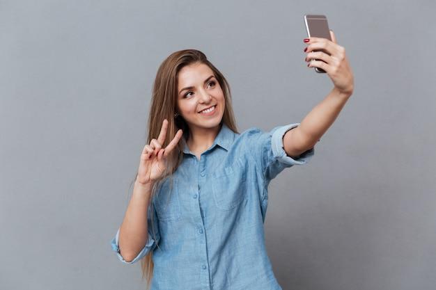 スマートフォンでselfieを作るシャツで笑顔の女性