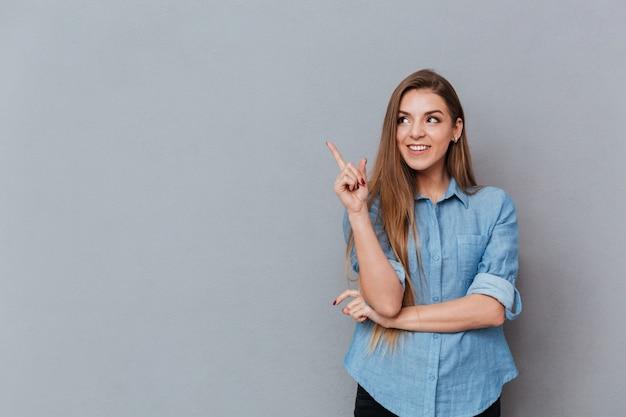 スタジオでポーズのシャツで笑顔の女性