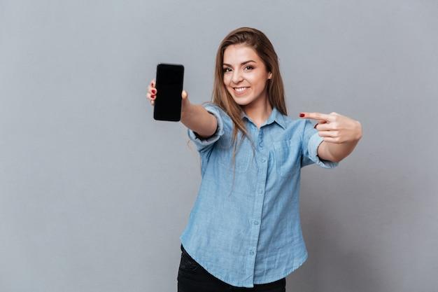 空白のスマートフォンの画面を示すシャツの笑顔の女性