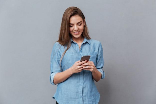 電話を使用してシャツを着た笑顔の女性