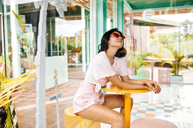 屋外カフェに座っているショートパンツで笑顔の女性。夏の週末を楽しんでいるピンクのサングラスの夢のような女性。