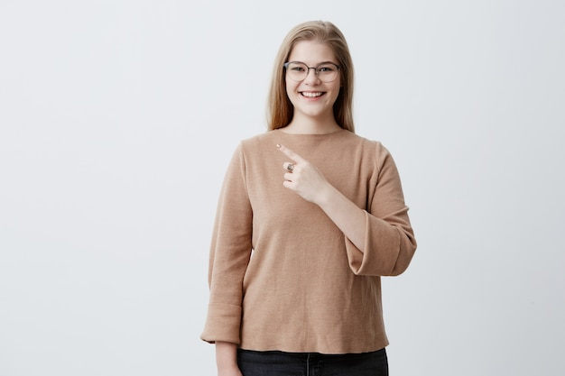 Улыбается женщина в свитер и стильные очки с прямыми светлыми волосами, указывая на пустой белой стене, демонстрируя что-то. жизнерадостная женщина показывая с пальцем передней части на серой предпосылке.