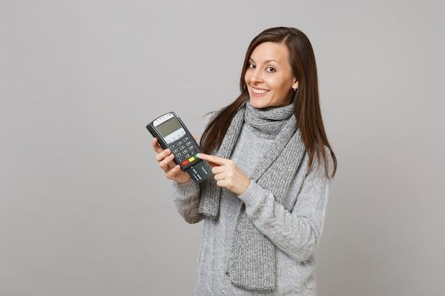 스웨터 스카프를 두른 웃는 여성은 처리하기 위해 무선 현대식 은행 결제 단말기를 들고 회색 배경에 격리된 신용 카드 결제를 받습니다. 라이프 스타일, 사람들의 진심 어린 감정, 추운 계절 개념.
