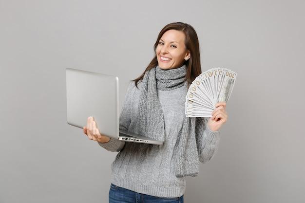 ラップトップpcコンピューターで作業しているセーターの笑顔の女性は灰色の背景に分離されたたくさんのドル紙幣現金お金を保持します。健康的なライフスタイル、オンライン治療コンサルティング、寒い季節のコンセプト。