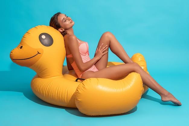 Улыбающаяся женщина в купальнике сидит с закрытыми глазами на желтой надувной утке