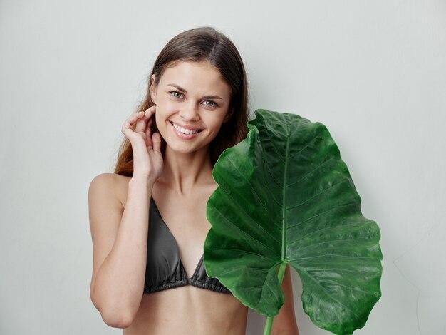 緑の葉と水着で笑顔の女性は髪の魅力をまっすぐにします