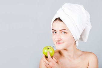 Smiling woman in towel holding apple