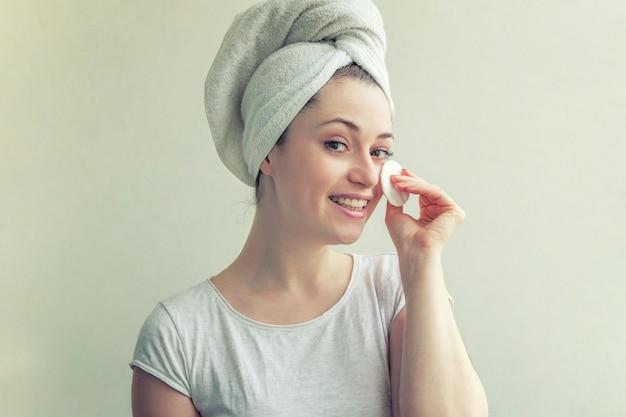 白い背景に分離された綿のパッドでメイクアップを柔らかく健康的な皮膚の除去で頭の上のタオルで笑顔の女性