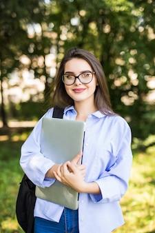 Улыбающаяся женщина в прозрачных очках стоит со своим ноутбуком в парке