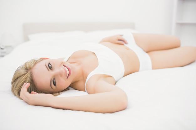 침대에 누워 속옷에 웃는 여자