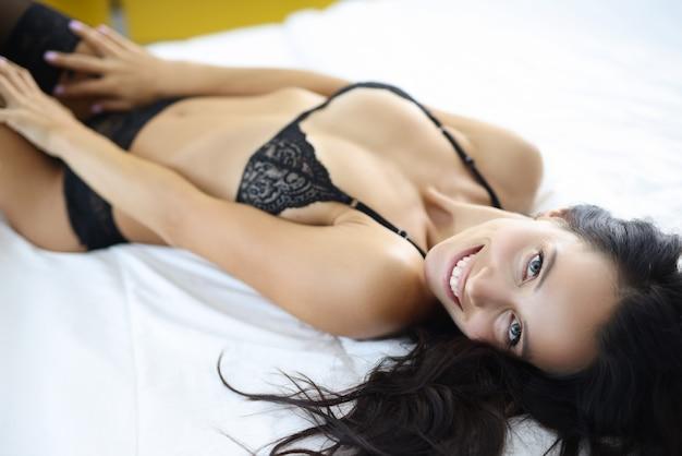 下着の笑顔の女性はベッドに横たわっています