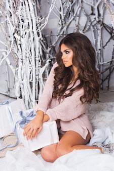 따뜻한 아늑한 니트 핑크 스웨터 흰색 선물 상자 앉아 들고 웃는 여자