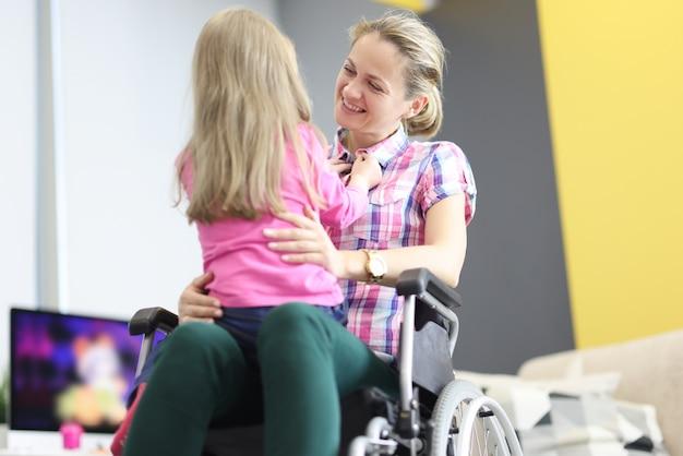 휠체어에 웃는 여자는 어린 소녀를 안 아