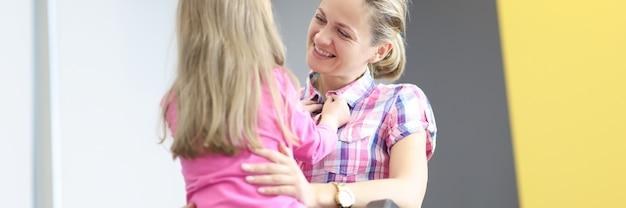 車椅子の笑顔の女性が小さな女の子を抱きしめます