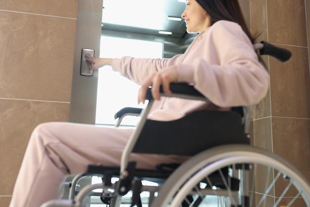 휠체어에 웃는 여자는 엘리베이터의 버튼을 누르면
