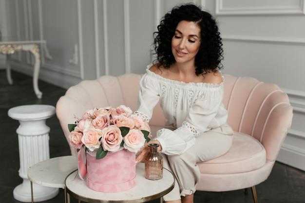 ピンクのソファに座って、ベルベットの箱のピンクの花に触れる白いブラウスで笑顔の女性