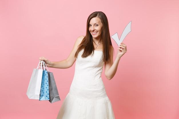 Улыбающаяся женщина в белом платье держит галочку, разноцветные пакеты с покупками после покупок