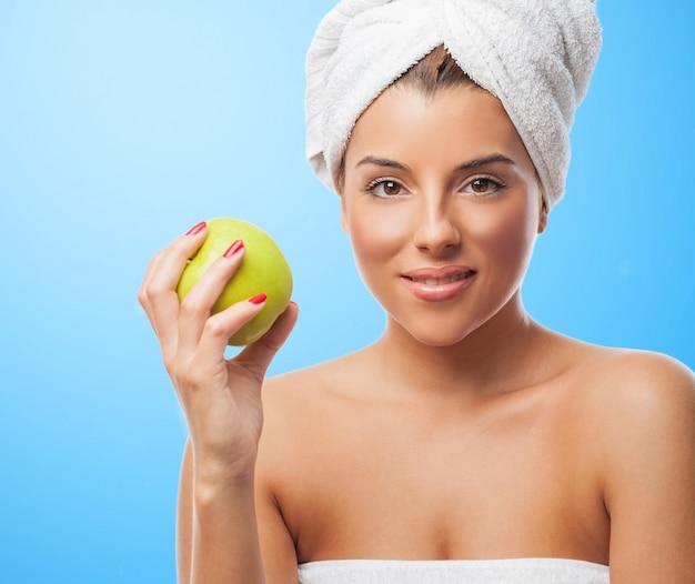 リンゴの白いタオルで笑顔の女性