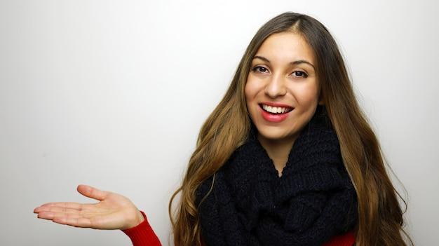 Улыбающаяся женщина в зимней одежде, представляя что-то на пустой ладони