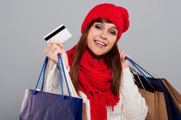 Улыбающаяся женщина в зимней одежде показывает кредитную карту и держит сумки для покупок