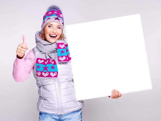 冬のアウターウェアの笑顔の女性は、親指を立てるサインでプラカードを保持します