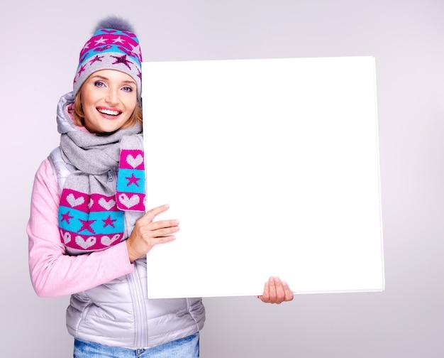 Улыбающаяся женщина в зимней верхней одежде держит в руках белый плакат