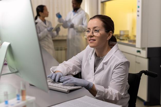 作業環境でコンピューター画面を見ている作業服で笑顔の女性
