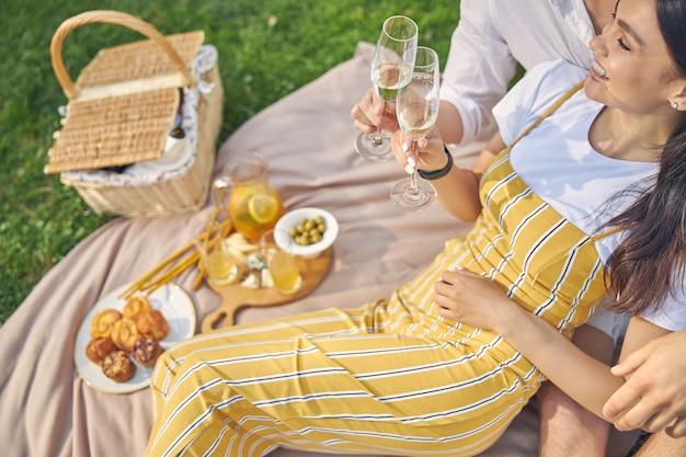 피크닉에서 사랑스러운 남자 친구와 함께 앉아 노란색 바지에 웃는 여자