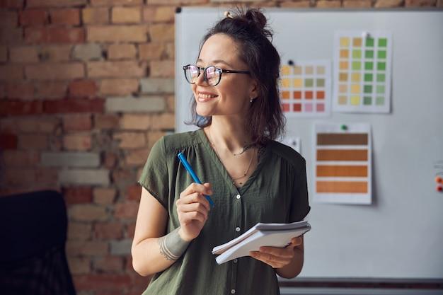 ペンとペンを保持している厄介な髪型とカジュアルな服装で笑顔の女性のインテリアデザイナーや建築家