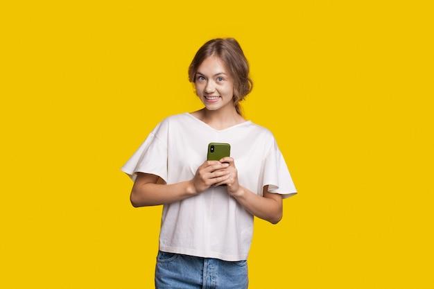 Улыбающаяся женщина держит телефон, позирует на желтой стене