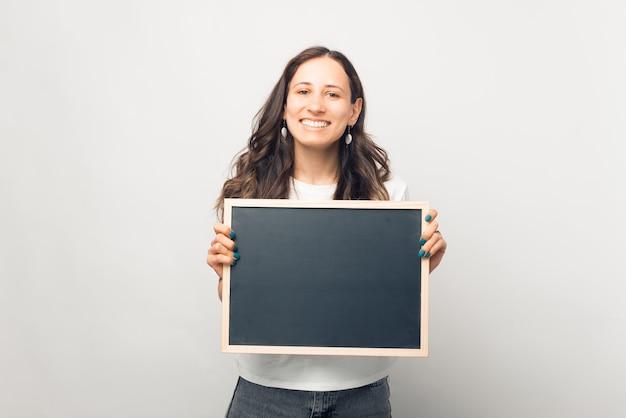 笑顔の女性はあなたのテキストのためのスペースと小さな黒板を持っています。