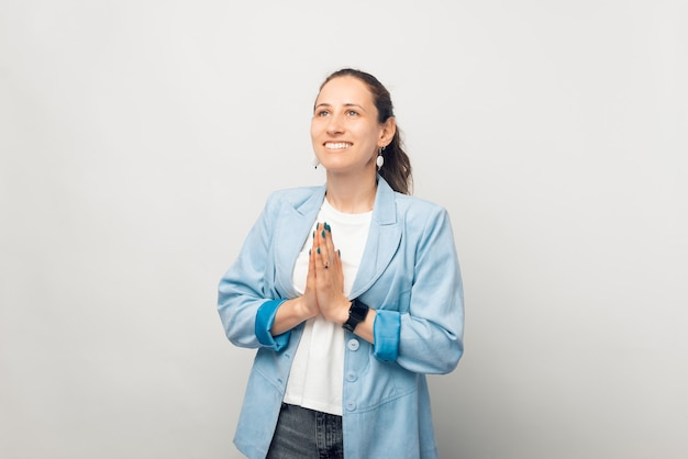 Smiling woman is making the prayer gesture, holding hands together.