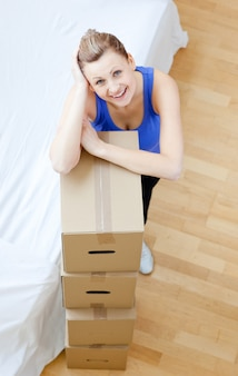 Smiling woman is moving various boxes