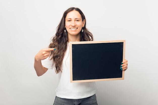 笑顔の女性があなたのテキストのためのスペースのある小さな黒板を指しています。