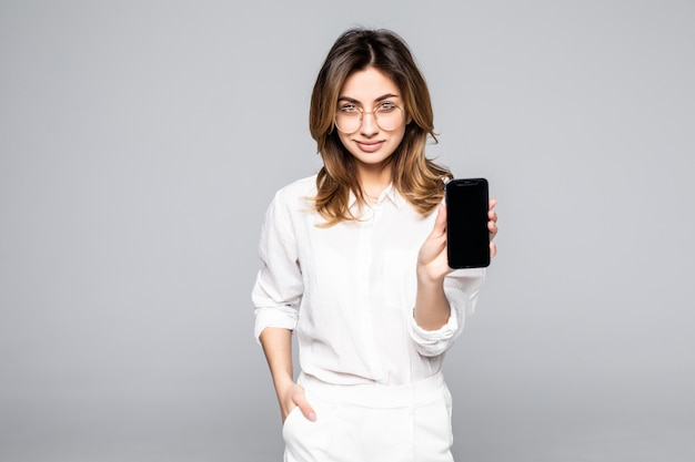 Smiling woman is pointing on smartphone standing on white wall.